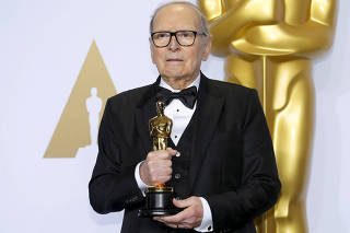 FILE PHOTO: Italian composer Ennio Morricone poses with his Oscar for Best Original Score for