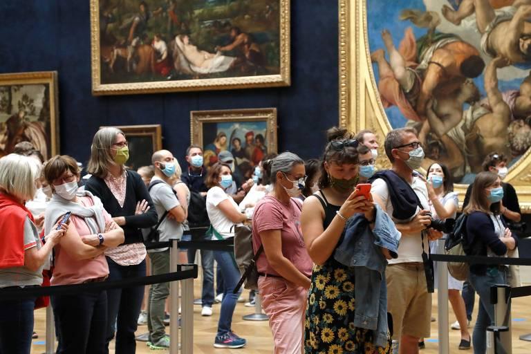 Aglomeração de pessoas usando máscaras faciais frente a quadros
