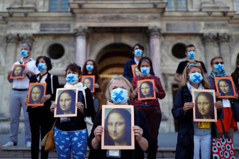 Paris tour guides hold posters depicting Mona Lisa painting by artist Leonardo da Vinci during an action at Le Louvre museum courtyard to warn on their working conditions as the museum reopens its doors to the public after almost 4-month closure due to the coronavirus disease (COVID-19) outbreak in France, July 6, 2020. REUTERS/Christian Hartmann ORG XMIT: PAR102
