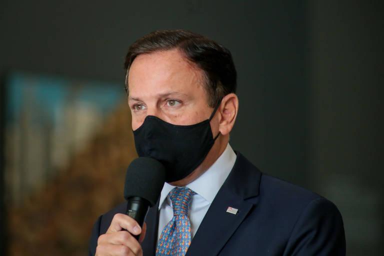 Doria, de máscara, segura um microfone enquanto fala