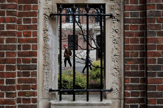 FILE PHOTO: Students and pedestrians walk through the Yard at Harvard University in Cambridge