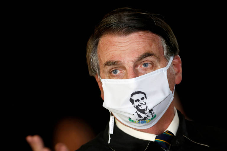Bolsonaro usa máscara com sua imagem em conversa com jornalistas, em maio