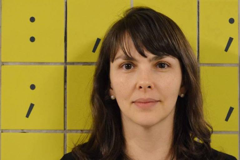 mulher de cabelo preto posa diante de azulejos amarelos