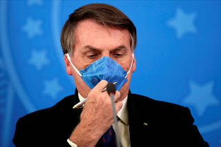 FILE PHOTO: Brazil's President Jair Bolsonaro adjusts his protective face mask at a press statement during the coronavirus disease (COVID-19) outbreak in Brasilia