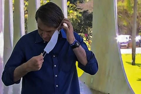 Screen grab of TV Brasil showing Brazilian President Jair Bolsonaro putting a face mask on as he prepares to speak with journalists at Planalto Palace in Brasilia on July 7, 2020. - Brazil President Jair Bolsonaro announced on Tuesday he had tested positive for the coronavirus but said he was feeling