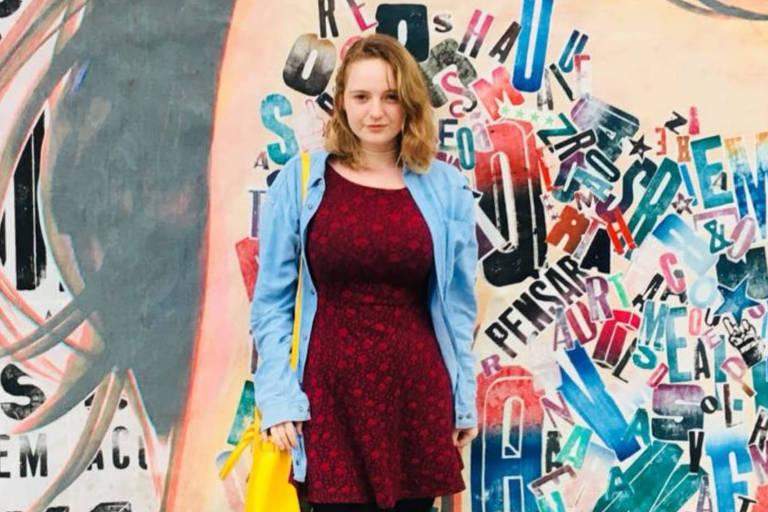 Jovem loira de vestido cor de vinho e jaqueta posa diante de um muro colorido por grafittis