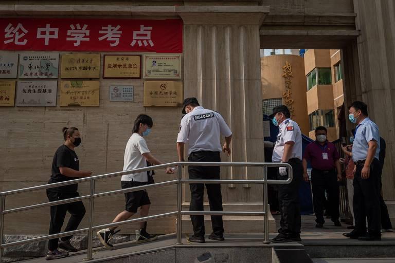 De máscara, fiscais conferem documentos de pessoas que sobe rampa que dá acesso a porta