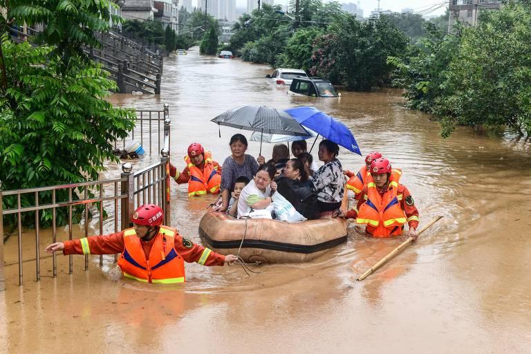 Pessoas são resgatadas de bote por profissionais após forte chuva em Jiujiang, na China