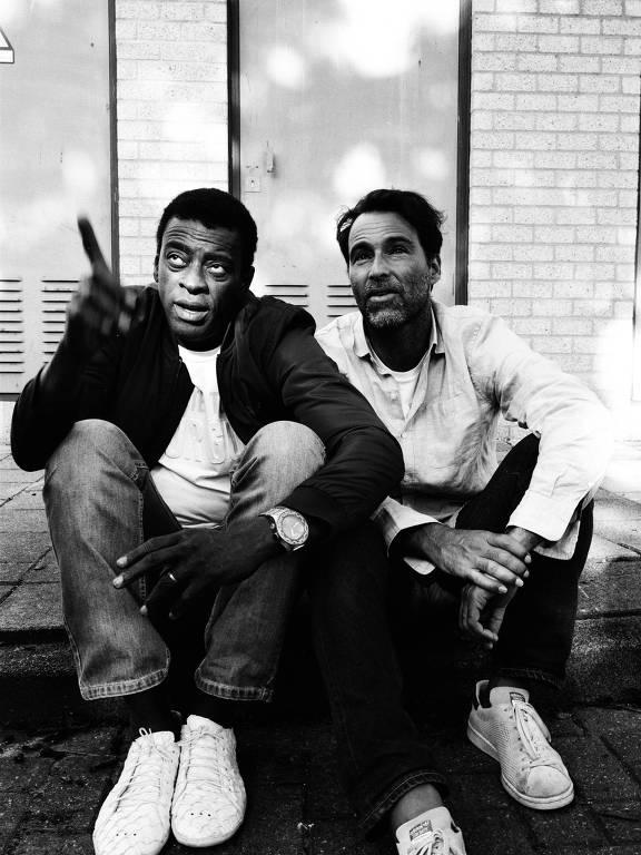Os artistas Seu Jorge e Rogê sentados na rua