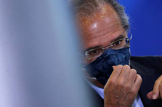 Brazil's Economy Minister Paulo Guedes adjusts his protective face mask before the inauguration ceremony of the new Communications Minister Fabio Faria (not pictured) at the Planalto Palace, in Brasilia