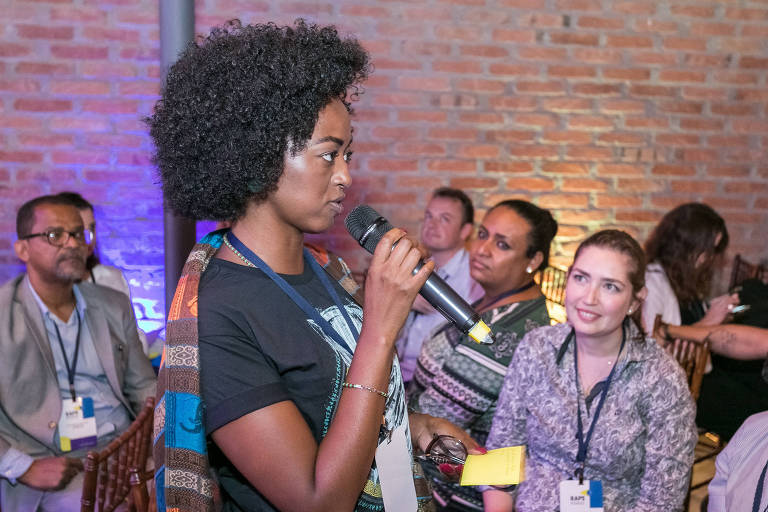 Aline falando ao microfone no meio de um plateia que a observa