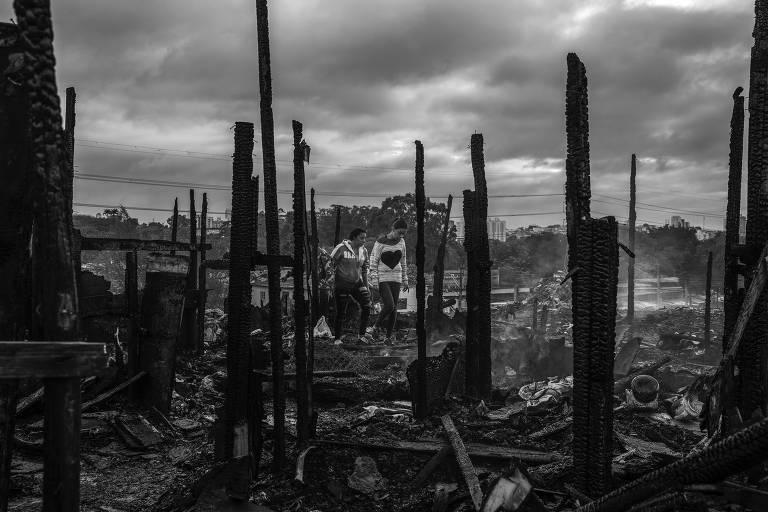 Moradores caminham em meio aos escombros do incêndio que destruiu parte dos barracos da favela da Zaki Narchi, na zona norte de São Paulo