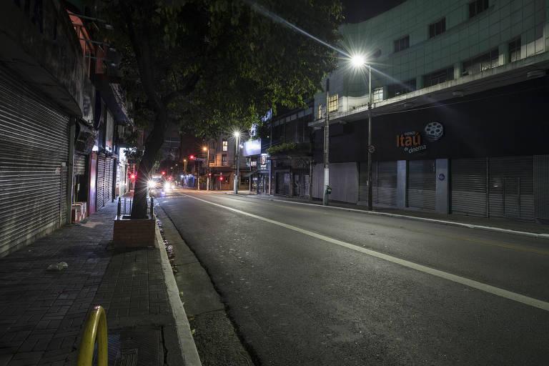 uma rua à noite com poucas luzes