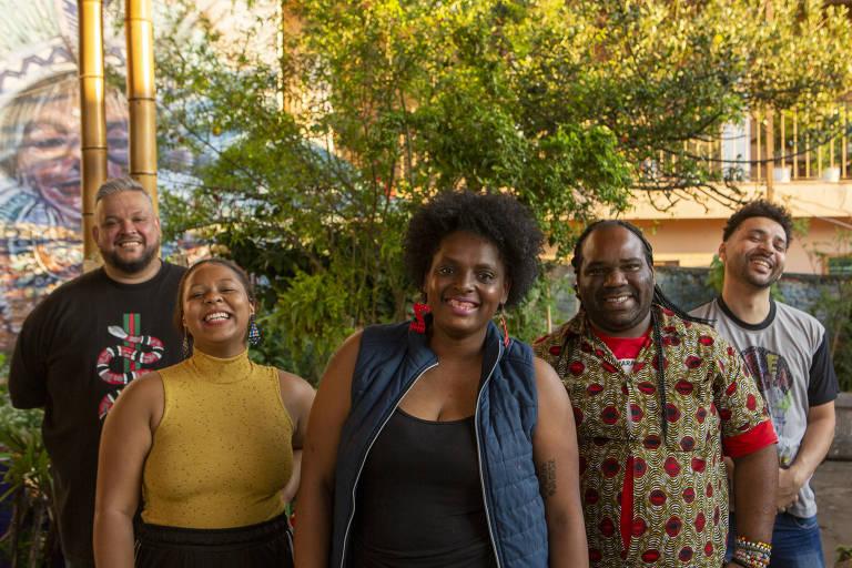 Grupo com duas mulheres e três homens, todos negros. Atrás deles, um arbusto e um grafite de uma índia