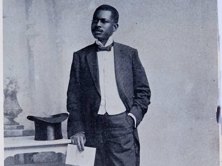 Homem negro de terno, se apóia em mesa sobre a qual está uma cartola em fotografia em preto e branco bastante desgastada pelo temo