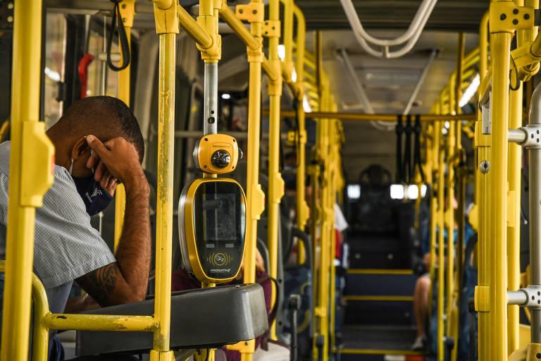 Cobrador aguarda passageiros em ônibus na cidade de São Paulo