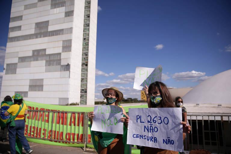 """Três mulheres seguram cartazes, o que está em evidência diz """"PL 2630 não, censura, não"""". Ao fundo se vê mais dois manifestantes, e o Senado Federal. O céu está azul."""