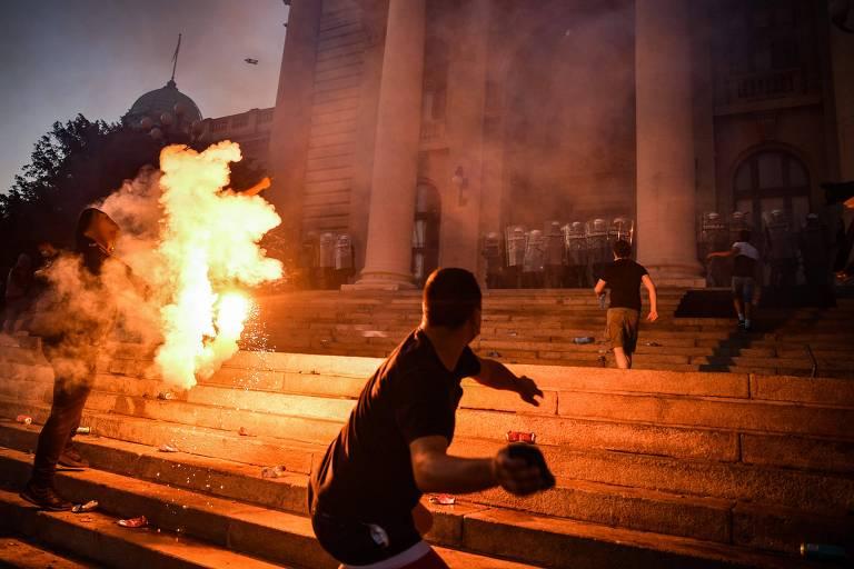 Manifestantes em confronto com a polícia na frente da Assembleia Nacional da Sérvia, em Belgrado