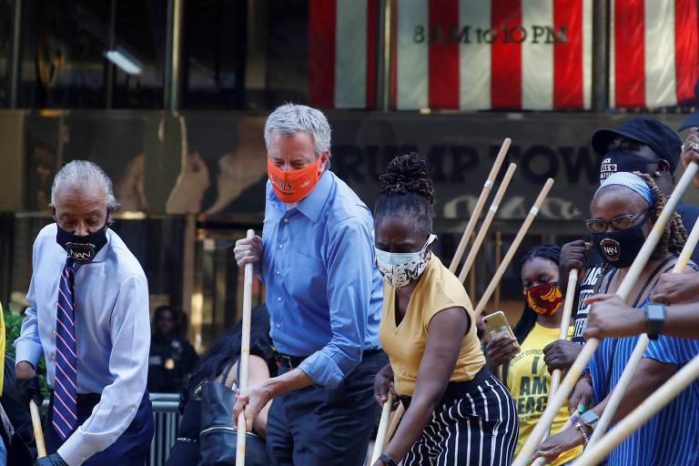 """O reverendo Al Sharpton (esq.), o prefeito de Nova York, Bill de Blasio, e sua esposa, Chirlane Irene McCray, pintam o slogan """"Black Lives Matter"""" em frente à Trump Tower"""
