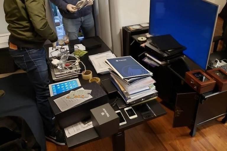 Na foto se vê escrivaninha com pilha de papel, notebooks empilhados, dois homens com luva analisam os itens.