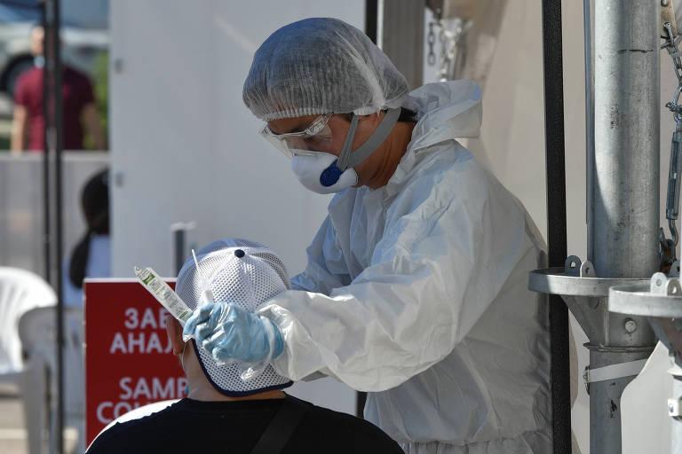 Profissional de saúde realiza teste de detecção de saúde em homem em Almaty, no Cazaquistão