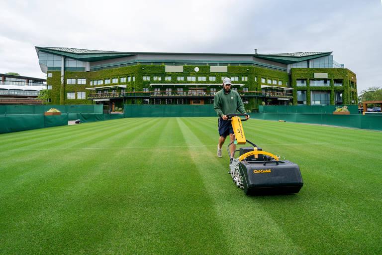 Homem passa máquina sobre a grama da quadra de tênis