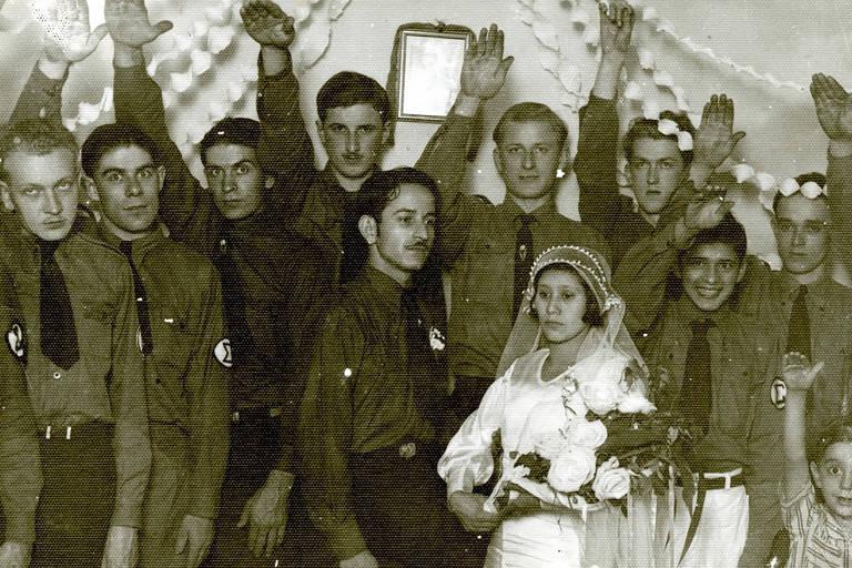 Homens com braços direitos levantados ao redor de uma noiva