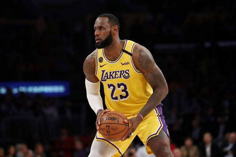 LeBron com o uniforme amarelo dos Lakers segura a bola