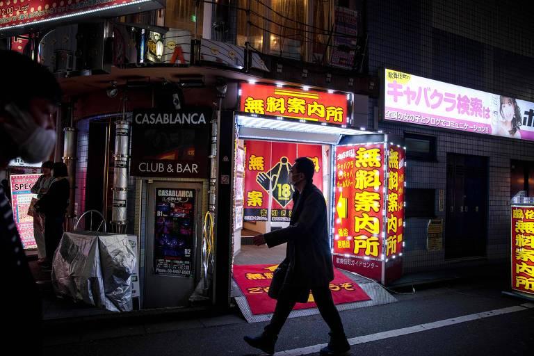 Foto tirada à noite mostra homem em frente a um porta com letreiros coloridos, com escritos em japonês