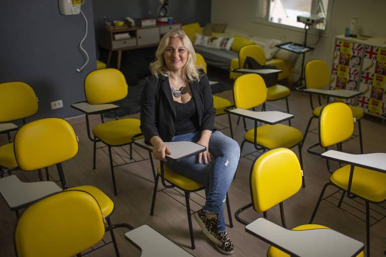 Mulher loira com blusa preta sentada em sala com cadeiras amarelas