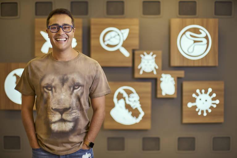 Homem com camiseta com estampa de leão e óculos, sorrindo