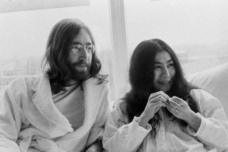 John Lennon escreve uma letra de música em uma folha de papel, ele está ao lado de Yoko Ono