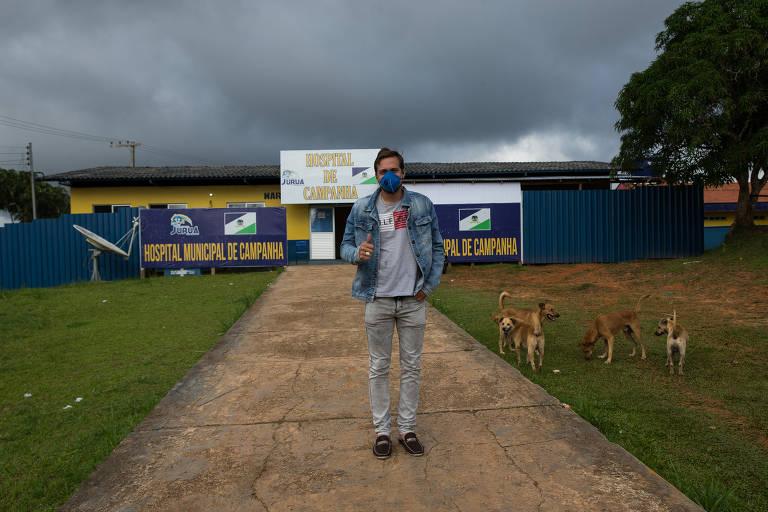 Homem jovem de máscara e jaqueta jeans em rua de terra batida diante de instalações de hospital de campanha que parece um ginásio