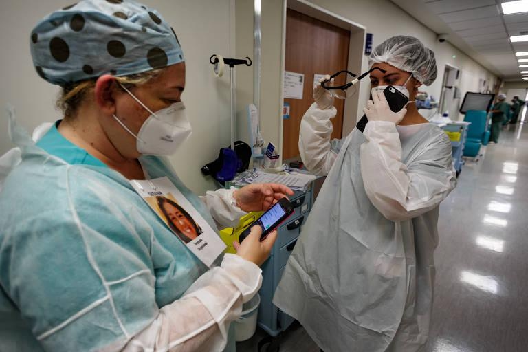 A médica Raissa Robles (à dir.) e a terapeuta ocupacional Tatiana Couto se preparam para entrar em um quarto de UTI do Hospital do Servidor Público