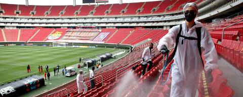 TOPSHOT - Guadalajara team cleaning staffers disinfect the areas for the football players, before the start of the Mexican football tournament match between Mazatlan and Atlas in Guadalajara, Jalisco state, Mexico, on July 7, 2020,amid the coronavirus pandemic. - The match was held at closed doors and respecting sanitary measures to prevent the spread of COVID-19. (Photo by Ulises Ruiz / AFP)