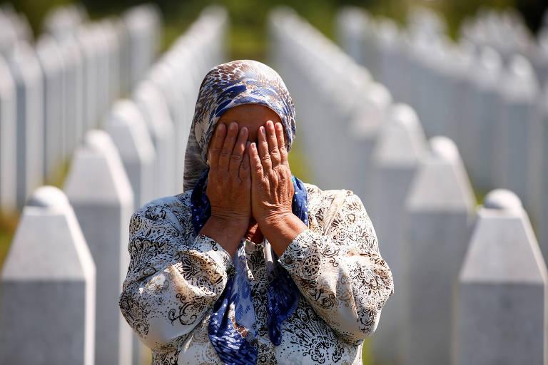 Mulher chora entre lápides brancas