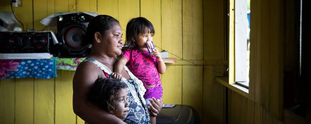 Mulher com menina pequena ao colo e outra um pouco maior ao lado, em uma sala de ripas de madeira amarela, observa movimento da janela, iluminada pelo sol