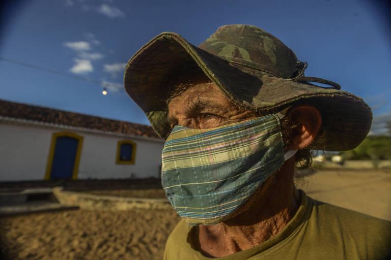 Senhor de chapéu e máscara olha para o sua direita, com sol baixo no rosto, em frente à uma casa branca.