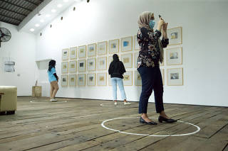 Visitors wearing protective face masks look at art painted by Indonesian artist Hanafi at Kertas Gallery as their stands in a circle as physical distancing during an exhibition in Depok