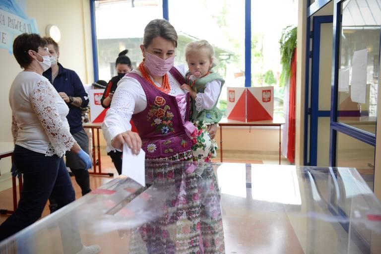 Mulher em vestes tradicionais segura bebê enquanto coloca voto na urna