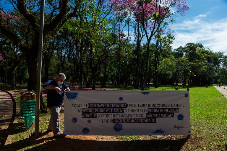 Funcionário arruma faixa que alerta sobre a importância das medidas de prevenção contra a Covid-19 no Parque Ibirapuera