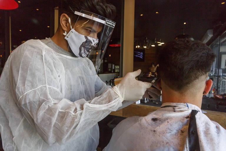 Marcos Vinícius da Silva usa corretamente o escudo fácil, com máscara de proteção, para cortar cabelo em barbearia da zona sul de São Paulo