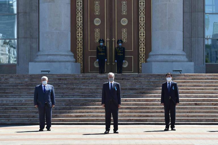 Presidente, ao centro, junto a altos-oficiais do governo cazaque frente a grande construção de mármore