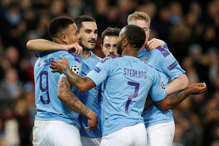 Cinco jogadores com uniforme azul claro se abraçam