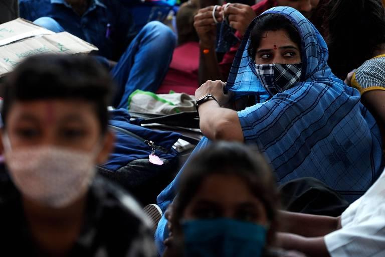 Pessoas esperam para embarcar em um trem especial para Rajasthan, na Índia, após o governo local ter aliviado a quarentena imposta no país para conter o coronavírus