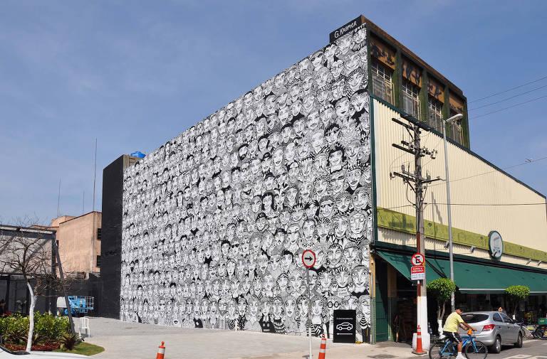 Foto mostra a fachada de um prédio onde está pintado um mural com vários rostos