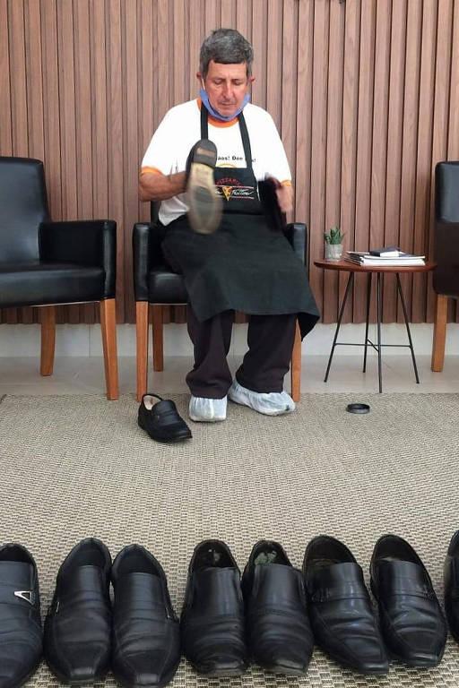 Um engraxate lustra sapatos sentado em uma cadeira de escritório. À frente dele, estão pares de sapato enfileirados