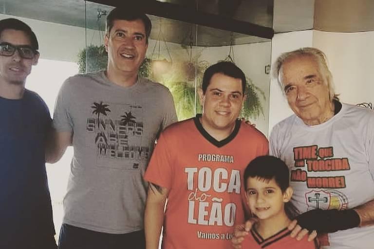 O maestro João Carlos Martins, com suas luvas biônicas, recebe três torcedores da Leões da Fabulosa, além do filho João Carlos Assumpção, em seu apartamento.