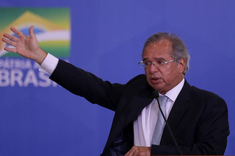 Ministro da Economia Paulo Guedes levanta o braço direito para cima enquanto fala na solenidade de anúncio da prorrogação do programa de Auxílio Emergencial, no Palácio do Planalto