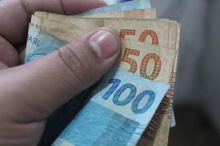Mão esquerda segura maço de dinheiro com nota de R$ 100 à frente de de R$ 50